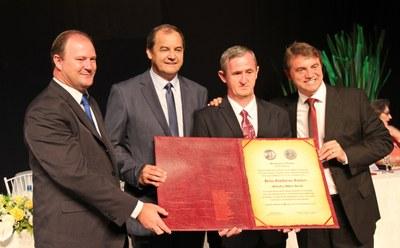 Hélio Guckert recebe a honraria do presidente Ademar, vice-prefeito Adelar e prefeito Beto